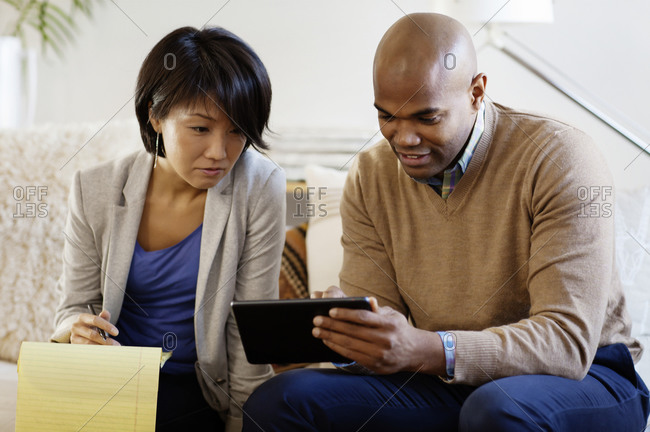 Two employees in office sharing tablet