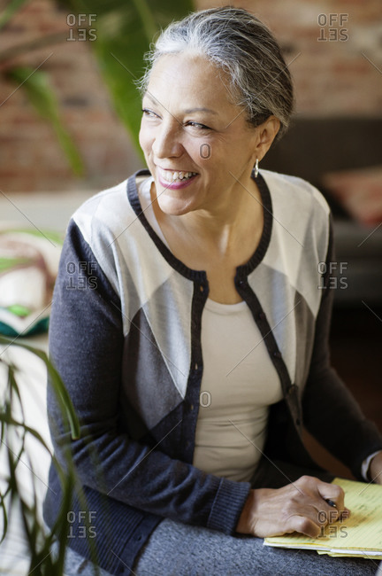 Older woman in office holding notepad and smiling