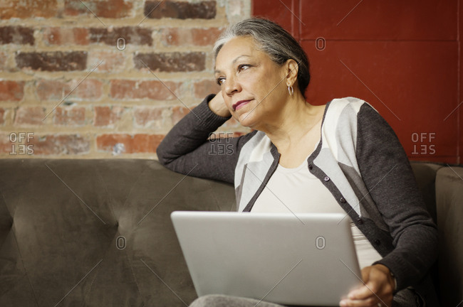 Woman thinking on couch with laptop