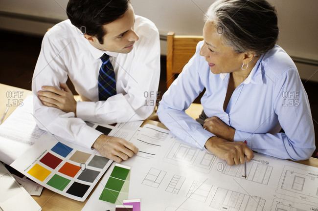 Man and woman in office discussing designs
