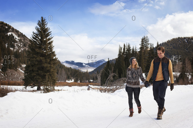 Young couple walking in snow in mountain field