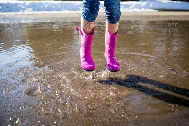 Child in pink boots jumping in a puddle