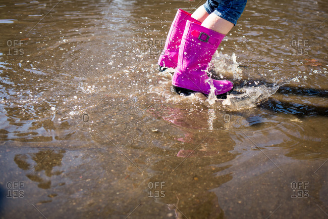 Splashing in a puddle with pink rubber boots