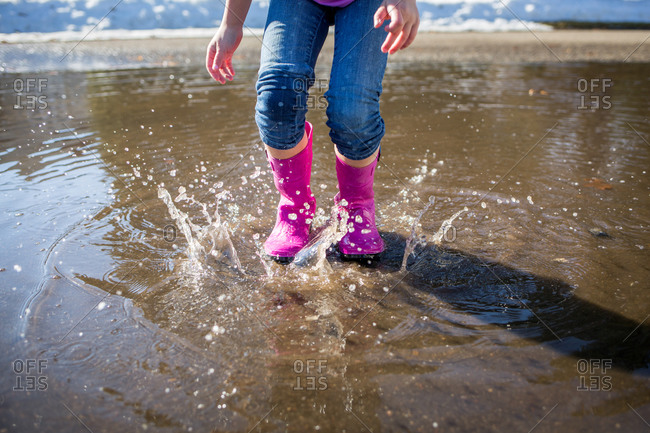 Girl splashing in a puddle with pink boots
