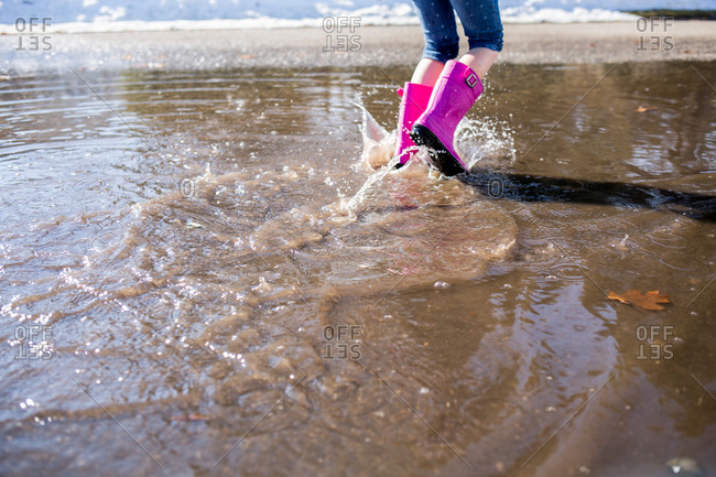 Girl walking through a puddle with pink boots