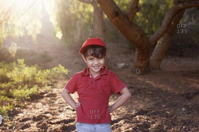 Portrait of boy in baseball cap in sunny woods