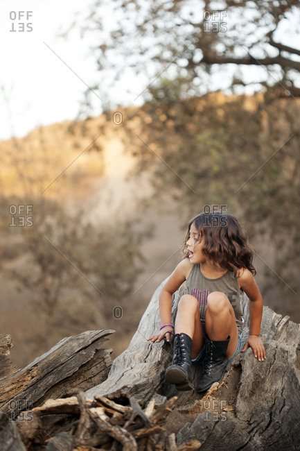 Girl climbing on tree stump in woods