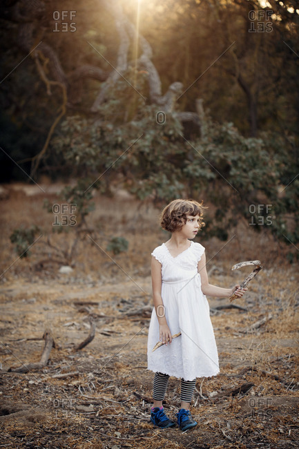 Girl holding stick in sun dappled woods