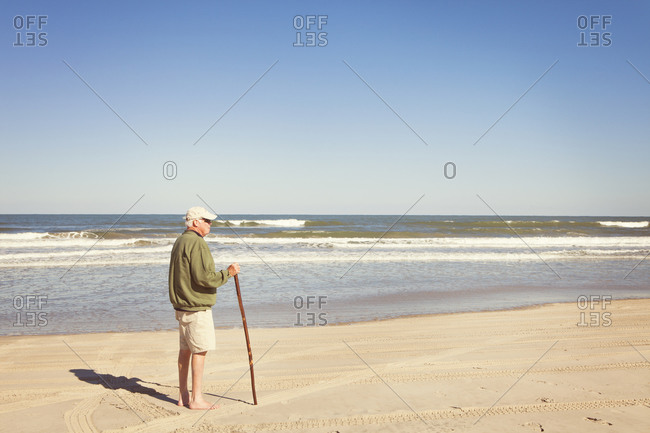 Old man standing on beach with cane