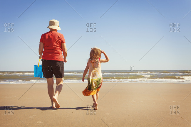 Grandmother and girl walking to the ocean