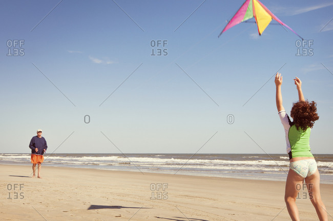 Grandpa and girl flying kite on beach