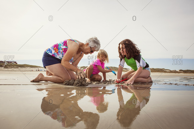 Grandma and girls digging in sand on beach