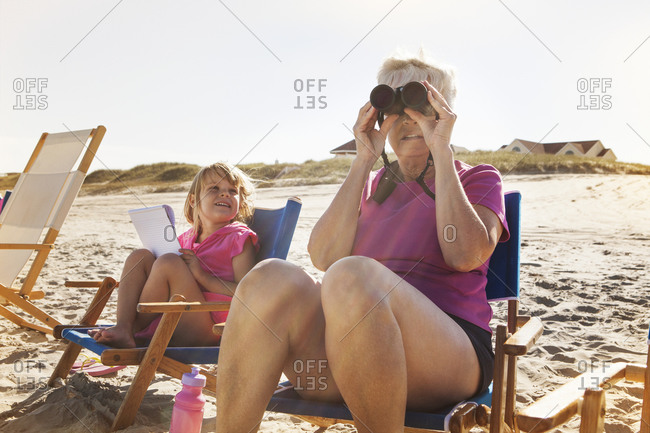 Grandma and girl sitting in beach chairs with binoculars