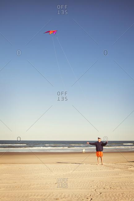 Man standing on beach flying kite