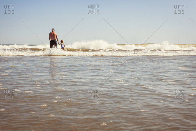 Grandpa and girl wading out to sea