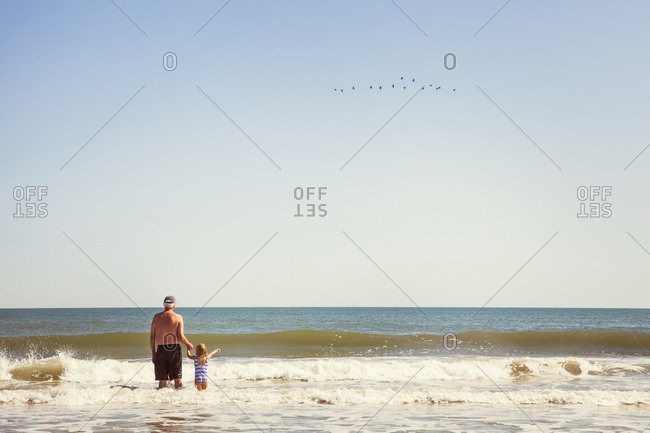 Grandpa and girl standing out to sea