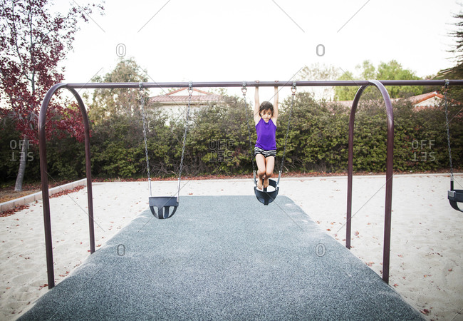 A little girl hangs from the top of a swing set