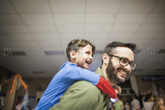 A father gives his son a piggyback ride