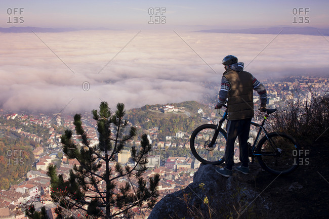 Mountain biker looking down at village from cliff edge