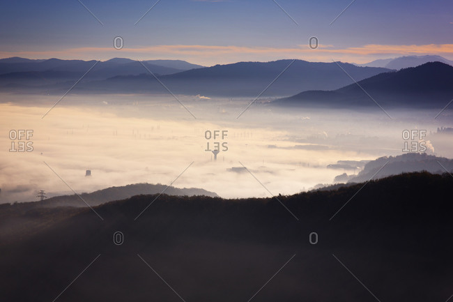 Mountains with factories below a cloud-obscured valley