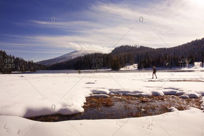 Woman walking in snowy mountain field near lake