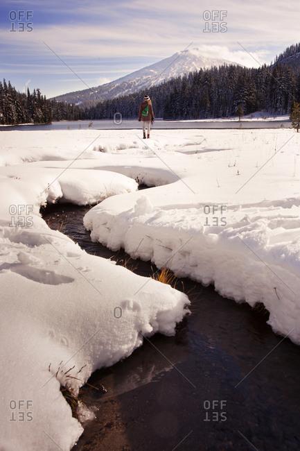 Woman walking near creek in snowy mountain field