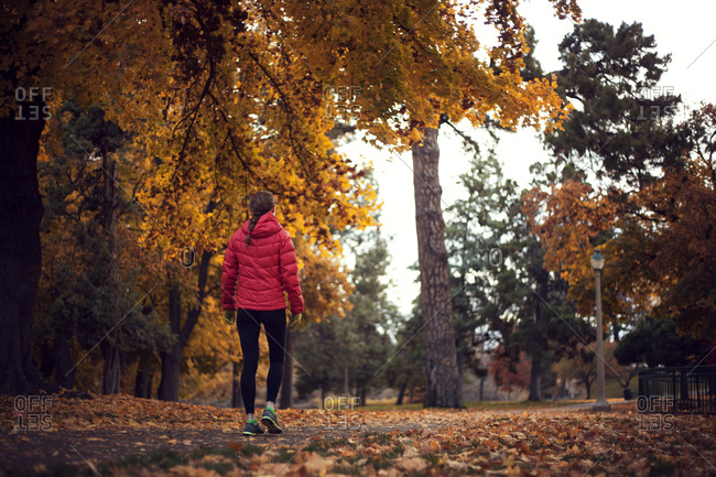 Woman walking along park path in fall