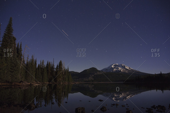 Shooting star over pristine mountain lake