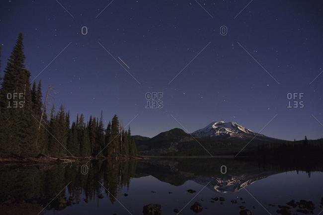 Shooting star over pristine mountain lake