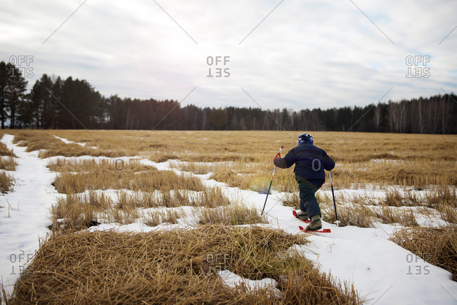 Boy using small skis in snowy field