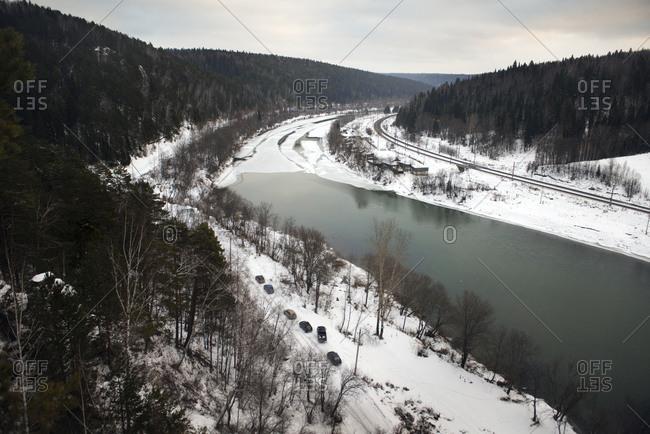 Road running along river through snowy mountain