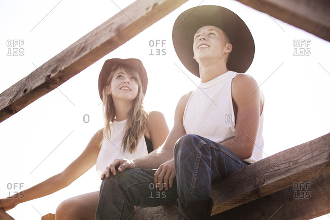 Two friends sitting on rural bridge