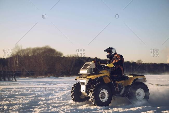 Man driving a four wheeler in the snow