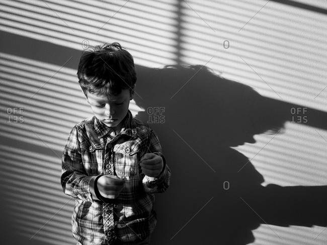 Young boy standing against a wall with shadows falling across
