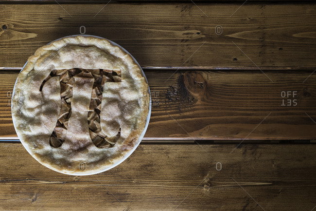 Overhead shot of an apple pie with a pi-shaped cutout