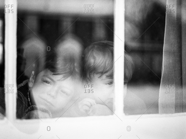Two boys looking out a window