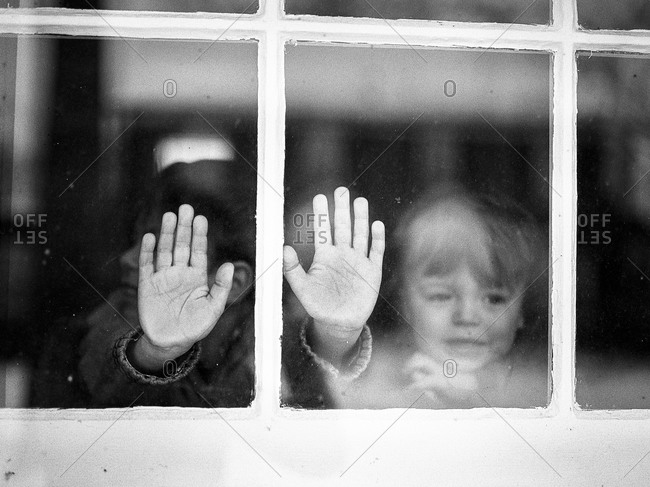 Child's hands on a windowpane from outside