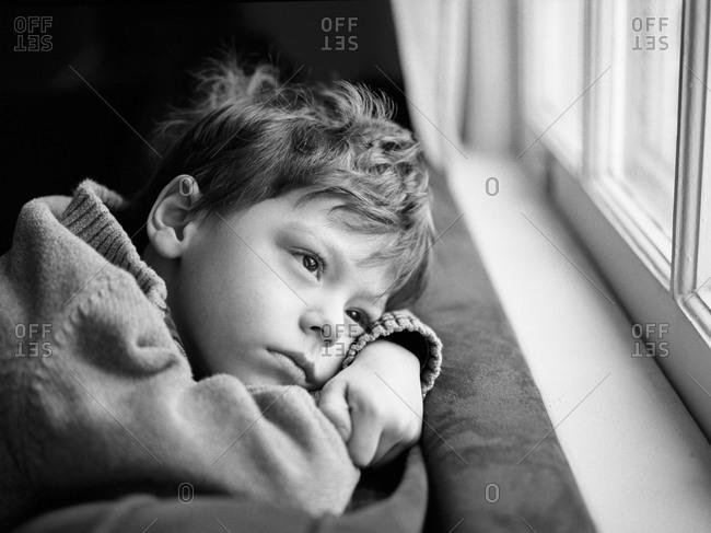 Daydreaming boy next to a window