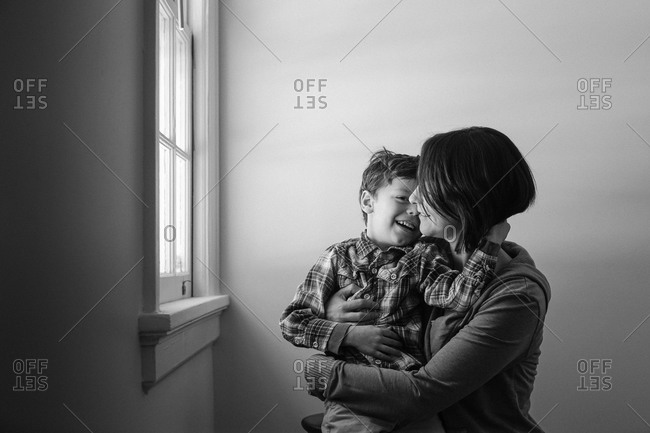 Affectionate portrait of mother and son by a window