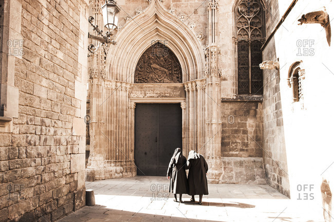 Two elderly nuns walking in church courtyard