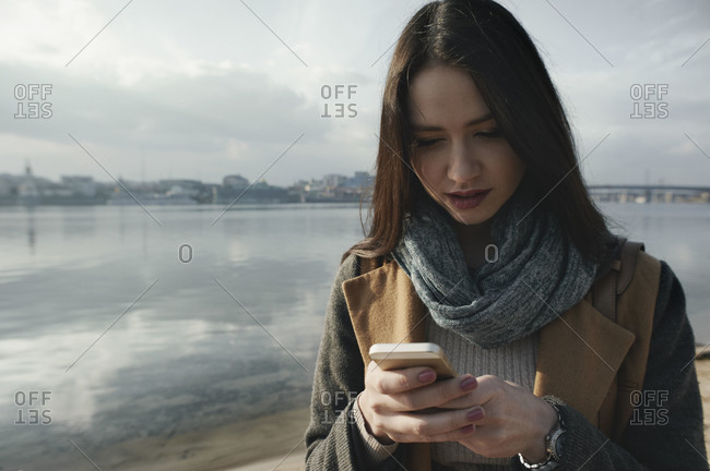 Woman by urban river using smartphone