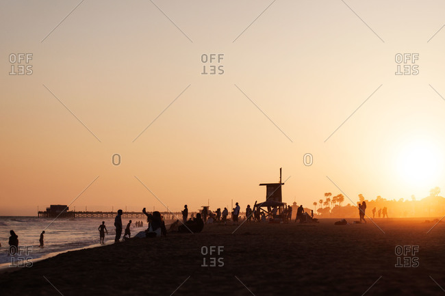 Beachgoers at sunset near a lifeguard stand and pier