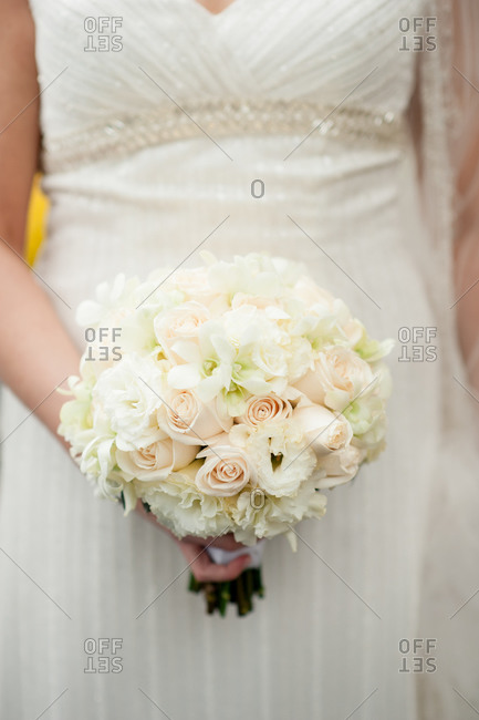 Bride in white gown holding bouquet of white and pale pink flowers