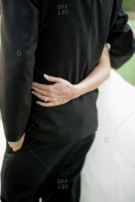 Back view of bride's arm around the waist of groom