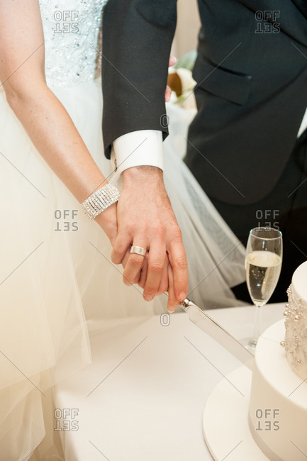 Bride and groom cutting cake together