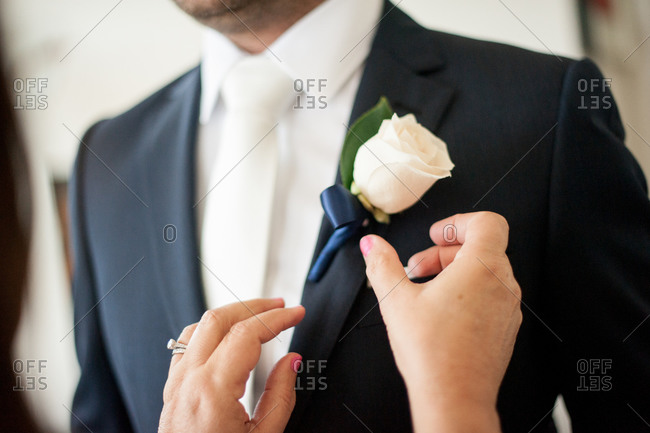 Woman pinning white rose boutonniere being pinned on the lapel of groom
