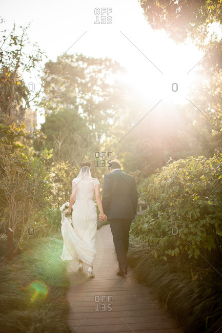 Bride and groom walking down a garden path on a sunny day