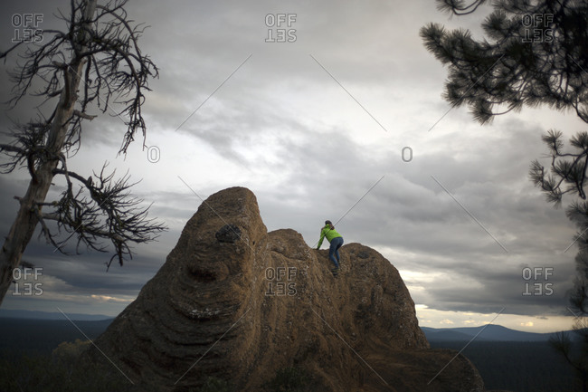 Woman climbing up a rock under a cloudy sky