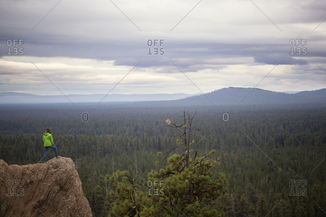 Woman standing on a rock formation overlooking a vast forest below