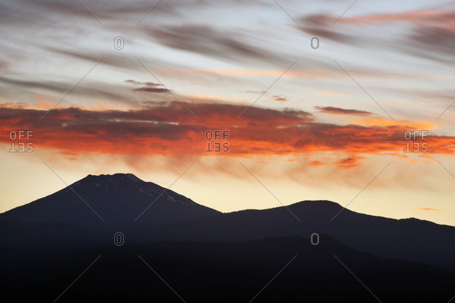 An orange cloud over mountains at sunset